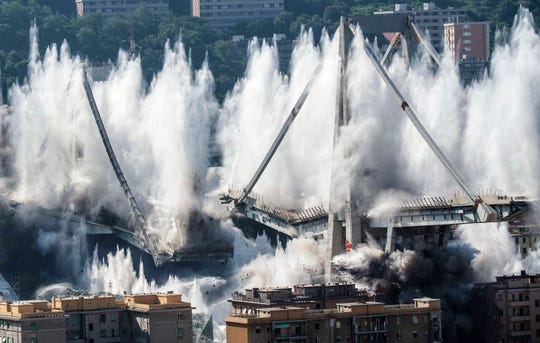 A cloud of dust rises as the remaining spans of the Morandi bridge are demolished in a planned explosion, in Genoa, Italy, Friday, June 28, 2019.