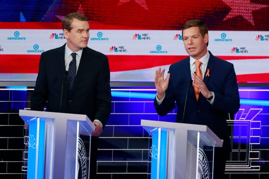 Democratic presidential candidate Rep. Eric Swalwell, D-Calif., right, speaks  as former Colorado Sen. Michael Bennet watches.