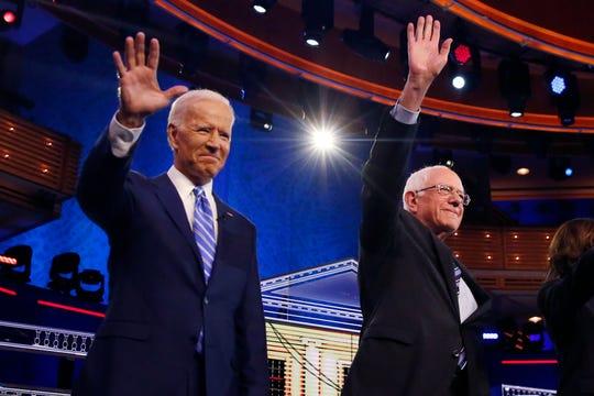 Democratic presidential candidates former vice president Joe Biden, left, and Sen. Bernie Sanders, I-Vt., wave before the start of a Democratic primary  debate.