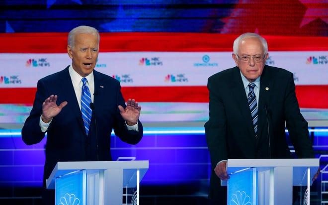 Democratic presidential candidate former vice president Joe Biden, left, speaks as Sen. Bernie Sanders, I-Vt., listens.