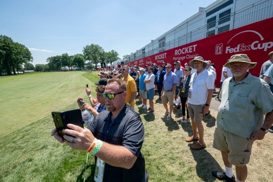 Fans try to get pictures of the golfers on the 10th hole during the Rocket Mortgage Classic.