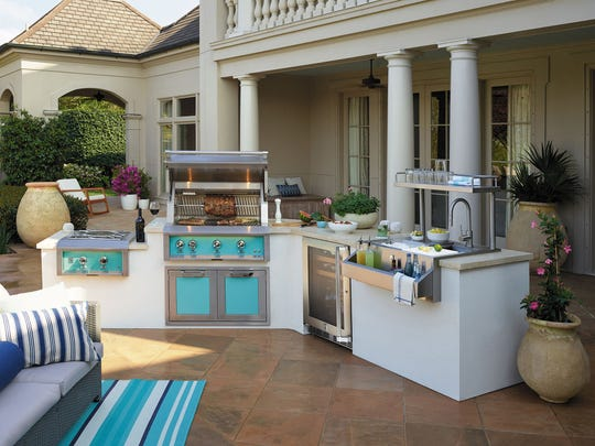 Hestan brings color to the outdoor grill and side burners. This built-in has a rotisserie, and the hood has motion-activated halogen lights. The outdoor refrigerator also is Hestan. Aqua inspires the palette for patio furnishings.