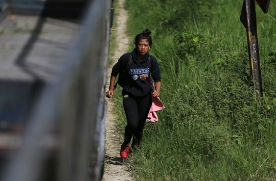 In this June 25, 2019 photo, 19-year-old Honduran Saily Yasm n Andino runs to climb aboard a freight train, near Salto de Agua, Mexico. When the train crowded with migrants began to move again, she hustled to clamber back aboard. But the train suddenly stopped and rolled back. She lost her grip and fell beneath its wheels.