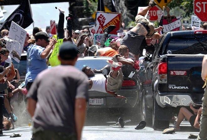 People fly into the air as a vehicle is driven into a group of protesters demonstrating against a white nationalist rally in Charlottesville, Va.  on Aug. 12, 2017.
