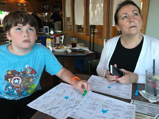 Just below the television screens at Frank's Press Box in Delta Township, 10-year-old Sam Bowen and Carol Wilson-Duffy listened attentively to the second night of Democratic presidential debates to catch some of the buzz words listed on their handmade debate Bingo sheets. Among the keywords: criminal justice, reparations, healthcare, Iran and Russia.