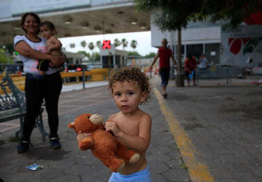 Eighteen-month-old Sergio Jr. from Cuba plays as he stands with other migrants waiting their turn to request asylum in the U.S., at the entrance to the Puerta Mexico bridge that crosses over the Rio Grande, in Matamoros, Tamaulipas state, Mexico, Wednesday, June 26, 2019.