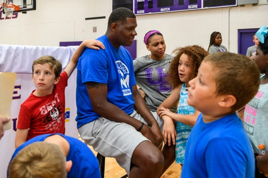 Walter McCarty, center, is surrounded by children from the Dream Center following the McCarty Leadership Academy basketball camp held at UE's Carson Center in Evansville, Ind., Friday, June 28, 2019. Children from the Boys & Girls Club of Evansville, Dream Center and the YMCA were invited to the camp to meet UE basketball players and sharpen their basketball skills.