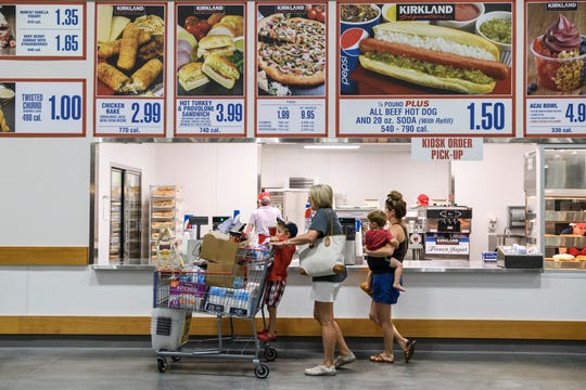 "Jaxon Stern, 4, from left, Nicole Toone, Sawyer Stern, 2, and Victoria Stern order lunch at Costco's food court while shopping in the new Evansville store, Friday, June 28, 2019. They ordered a few ""famous"" $1.50 hot dogs."