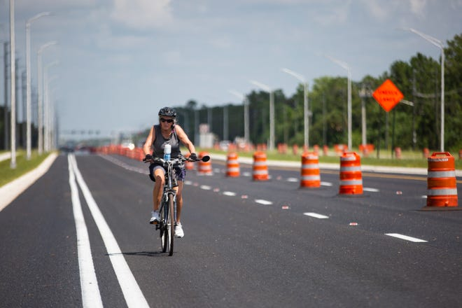 Jean Reichert of Fort Myers rides her bike, Friday, June 28, 2019, along State Route 82 between Gateway Boulevard and Griffin Drive in Lehigh.