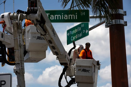 Lee County Department of Transportation signal technicians install road signs, Friday, June 28, 2019, at the intersection of Pondella Road and US 41 in North Fort Myers.