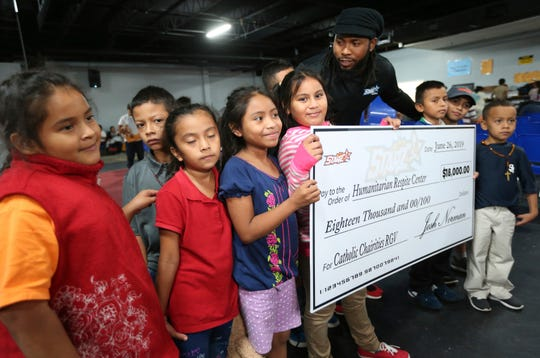 Washington Redskins cornerback Josh Norman speaks with children from Central America at the Humanitarian Respite Center in McAllen, Texas, where he donated $18,000 on Thursday, June 27, 2019. (Delcia Lopez/The Monitor via AP)