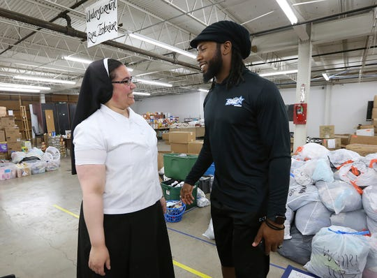 Sister Marie Jose De La Rosa, from New Jersey, chats with Washington Redskins cornerback Josh Norman at the Humanitarian Respite Center in McAllen, Texas, where he donated $18,000 on Thursday, June 27, 2019. (Delcia Lopez/The Monitor via AP)