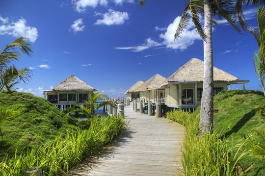 A set of bungalows offer shade to travelers along this wooden walkway in Samoa