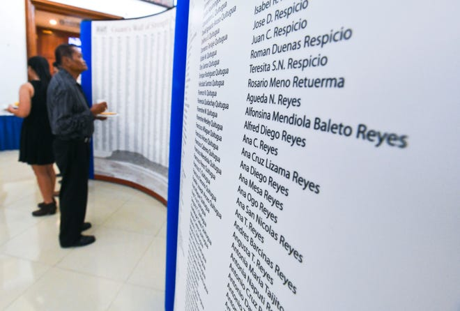 War survivors and other visitors search for names on the Guam's Wall of Strength: Names Never Forgotten panels that were placed on exhibit in the lobby of the Guam Congress Building in Hagåtna on in this June 28 file photo.