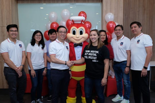 Jollibee Foods Corporation CEO Ernesto Tanmantiong, fourth from left, and Mañe'lu Executive Director Samantha Taitano, fourth from right, formalize the year-long partnership between the two organizations to bring joy to the youth of Guam.
