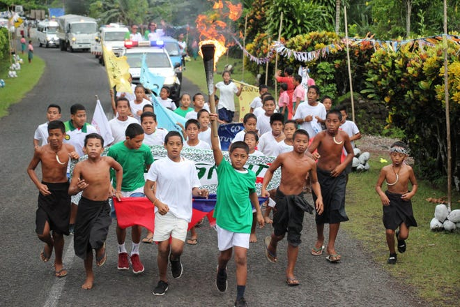 Children of the various nearby villages run with the Pacific Games Torch on Day 2 of the relay in Savaii.