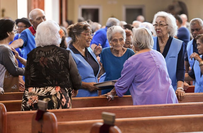 Parishioners and others offer one another a sign of peace during a Mass celebrated for war survivors at the Dulce Nombre de Maria Cathedral Basilica in Hagåtna on Friday, June 28, 2019.