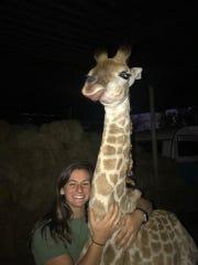 Bailey Stauffer, 20, hugs Remi, a young giraffe that's been bottle-fed. (June 2019)