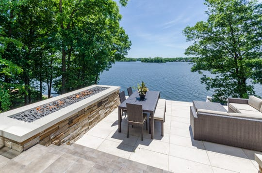 You can warm yourself by the outdoor fire pit as you admire the view of Geist Reservoir from the backyard on the home at 9343 Seascape Drive.