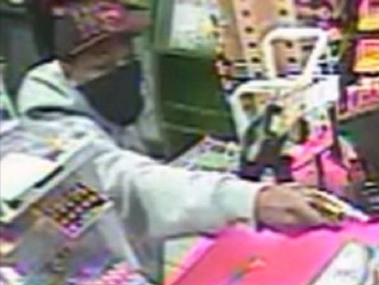 Indianapolis police released this image from a security camera showing a robber with a pistol at a gas station at 5220 W. Troy Ave. A clerk who was shot twice in the head died several days later at the hospital.