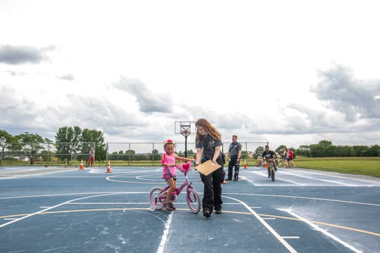 Iris Horton practices tight turns with help from Johnson County Ambulance Service paramedic Jessie Husmann, right, during the Summer Bike Rodeo, Thursday, June 27, 2019, at Wetherby Park in the South District of Iowa City, Iowa.