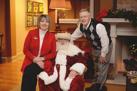 Leonie Hefley, vice president of Commercial Bank-Jackson, and her husband Mike Hefley sit with John Singleton (Santa Claus) at the bank.