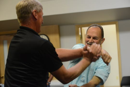 Bancorp South Market President Doug Roth and financial adviser Randy Wallace practice defense tactics during a demonstration at a Jackson Police Department fundraising event June 28, 2019.