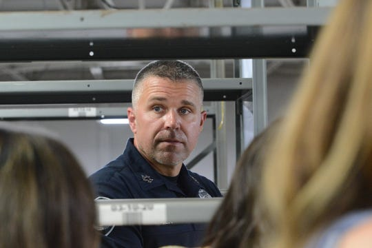 Jackson Police Chief Julien Wiser speaks to a group of civilians between records shelves at the Jackson Police Department garage during a fundraising event on June 28, 2019.