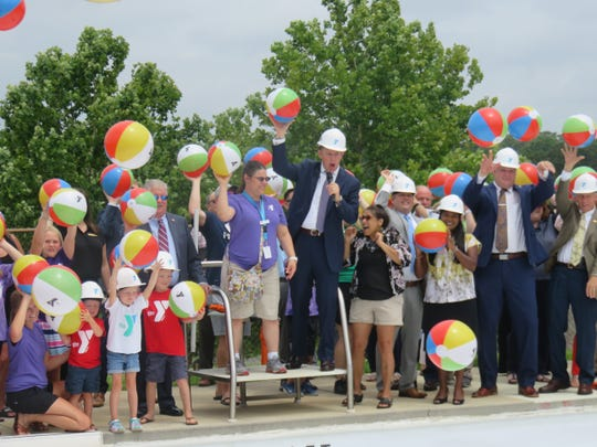 Emcee John Becker of WBIR Channel 10 leads participants in beach ball throw during ground breaking for new West Side YMCA pool on June 24, 2019.