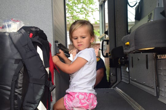 Annabelle Rader, 2, seems a little unsure about climbing aboard the fire engine, but curiosity got the better of her.