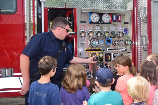 Karns Fire Department firefighter Jeff Lloyd answers the children's many questions patiently as he explains the different parts of a fire engine.