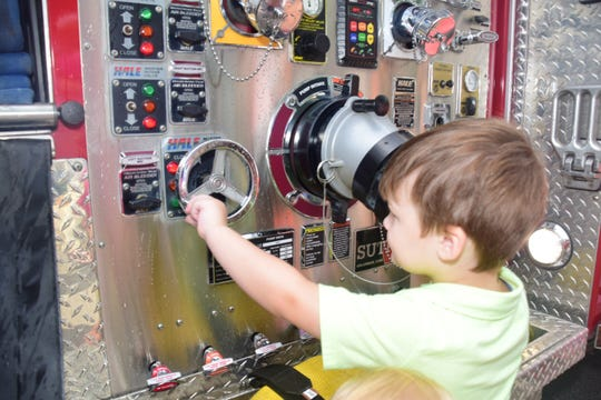 Owen Sexton, 2, seems fascinated by the many gears and gauges found on a fire engine.