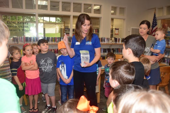 Using marbles and flour, Cindy Mize, outreach educator for The Muse Knoxville, demonstrates how craters were made on the moon.