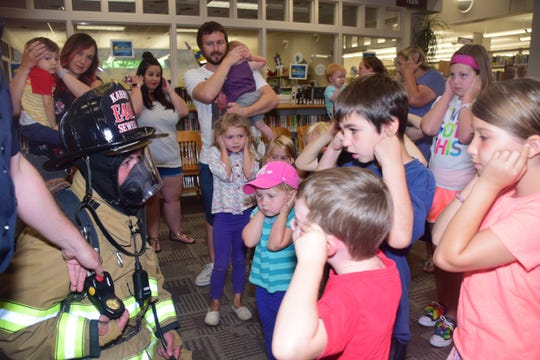 Karns Fire Department firefighter John Sewell allows the kids to see that he's a friend inside all the protective gear. He turned on his Personal Alert Safety System for the kids to hear.