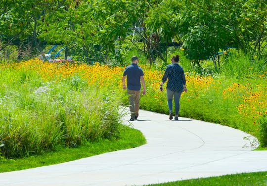 A couple walk along a completed portion of the Louisville Loop in the Parklands of Floyds Fork, next to a field of sunflowers.