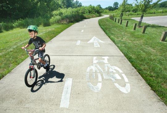Nathan Myers, 7, of Fisherville, bikes along a two-way bike path in the Parklands of Floyd's Fork on June 27, 2019.