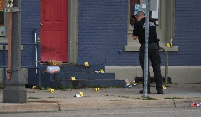 Members of the Lansing Police Department's Crime Scene Investigation  unit work at the site of an early morning shooting in the 400 block of East Cesar Chavez Avenue on June 28, 2019, in Lansing.