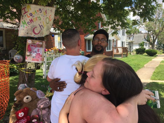Cllifton Williams, facing the camera, is comforted by Brian Hunt Friday outside the South Foster Street house where Chloe Williams, 3, died in an arson-related fire. At far right, Chloe's mother Kashawn Hawkins, is hugged by Brian Hunt's wife. Brian Hunt went into the burning house and carried out the babysitter's children who were standing in the front room. He said he did not know at the time Chloe was inside the house.