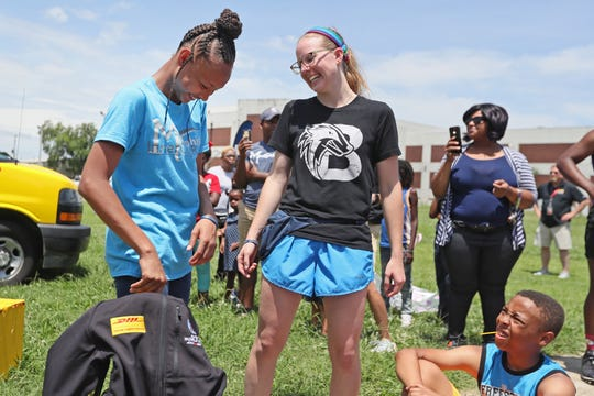 Jamiyah Brown, 11, a member of Memphis' Inner-City rugby program, is surprised with the announcement that she will travel to Japan to represent DHL at the Rugby World Cup. The trip came courtesy of a nomination from her coach Allison Hitchcock, right, who praised Brown, the only female member of the team, for her leadership as the team's captain.