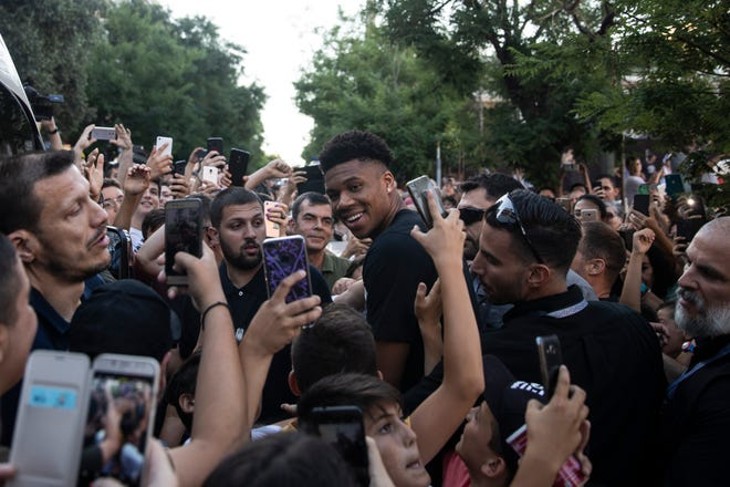Giannis Antetokounmpo is surrounded by fans as he leaves a basketball court in Athen on Friday. Antetokounmpo is in Greece to attend a 3x3 baseball tournament which he sponsors.