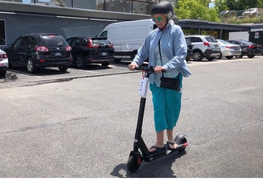 Victoria May rides a scooter with a free helmet provided by Bird, on Thursday, June 27, 2019 in Nashville, Tenn.
