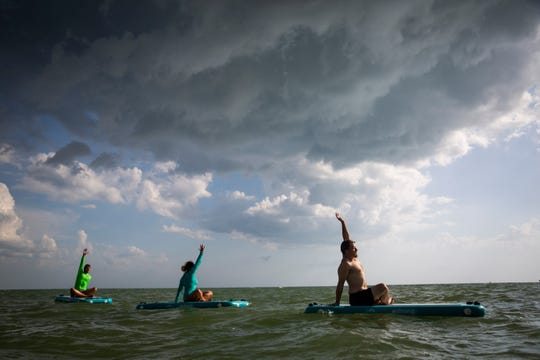 Anna Aaron, center, leads a paddle board fitness class for Jake Bredeson, left, and Corey Goerger, right, at Barefoot Beach in Bonita Springs on Thursday, June 27, 2019.