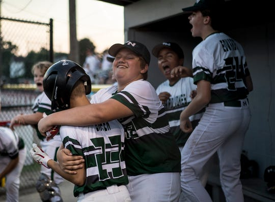 The Edward Jones team celebrates a run scored by Austin Breen (23) Thursday at Mound City during the 75th Licking County Shrine Varsity championship game. Edward Jones beat North Newark rival Park National Bank 6-4 for the title.