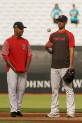 Boston Red Sox manager Alex Cora, talks with starting pitcher Rick Porcello during batting practice in London, Friday, June 28, 2019. Major League Baseball will make its European debut with the New York Yankees versus Boston Red Sox game at London Stadium this weekend. (AP Photo/Tim Ireland)