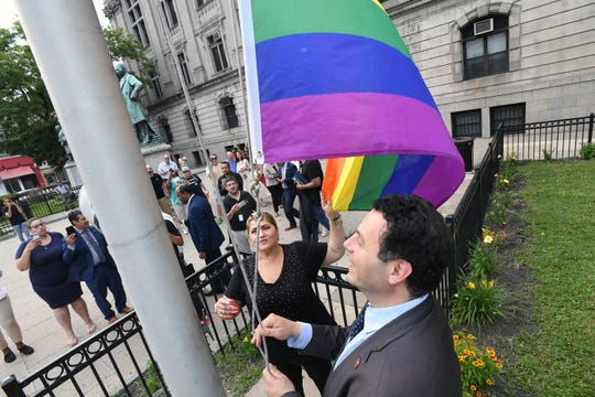Paterson Mayor Andre Sayegh and Paterson City Council President Maritza Davila raise a rainbow flag outside of City Hall in Paterson on Friday, June 28, 2019.