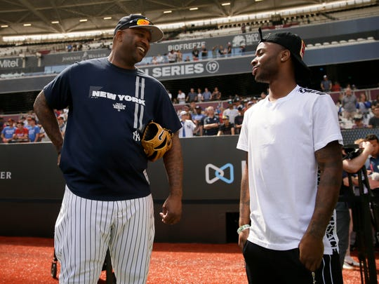 New York Yankees starting pitcher CC Sabathia, left, talks with England's soccer player Raheem Sterling during batting practice in London, Friday, June 28, 2019. Major League Baseball will make its European debut with the New York Yankees versus Boston Red Sox game at London Stadium this weekend. (AP Photo/Tim Ireland)