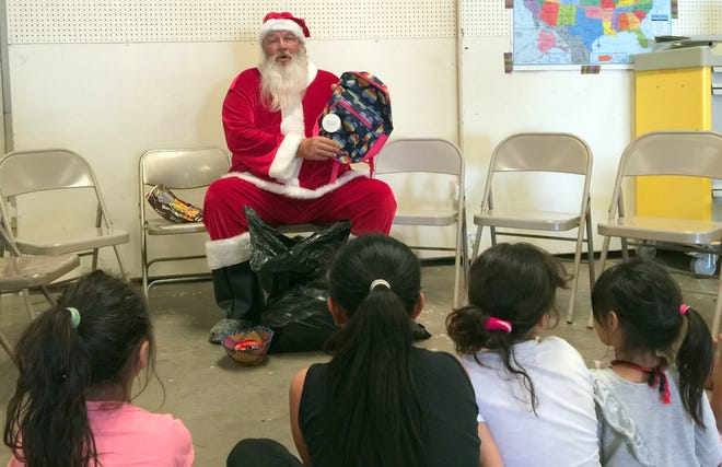 Santa Claus made a rare appearance in June to the Southwestern New Mexico State Fairgrounds in Deming, NM to visit with migrant children who are withfamilies at the migrant shelter. Santa (Keith Schwarzer) came bearing gifts for the children and visited with each one as though it was Christmastime in December. Schwarzer brought backpacks and an assortment of children's apparel, toys and personal hygiene items for the children to enjoy. Schwarzer is a Vietnam veteran who is active with veteran's organizations in the community.