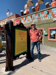 Teako Nunn, owner of Sparkys BBQ and Espresso in Hatch, stands with a replica New Mexico Historic Marker sign that was once a prop at the New Mexico Farm & Ranch Heritage Museum. The sign gives the history of the Sparkys site, and promotes the Farm & Ranch Museum.