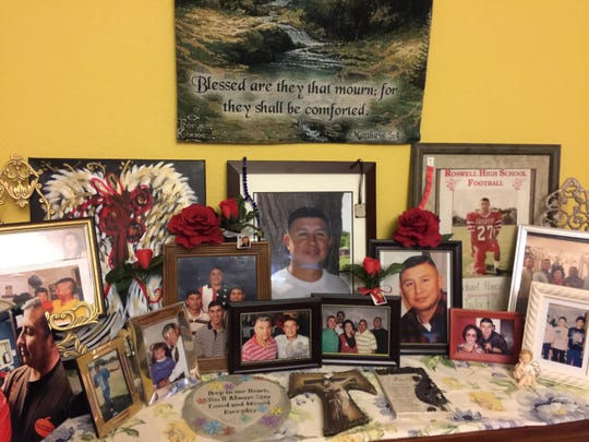 Photos of Michael Ponce, who died in an accident on US 285 on February 18, 2018, crowd a cabinet in his parents' dining room.