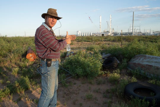 Craig Ogden on a neighbor's land, looking at oil processing facilities that Craig can see from his house.